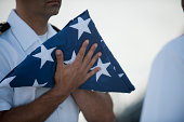 July 22, 2013 - U.S. Navy commanding officer of the guided missile frigate USS McClusky, holds the national ensign during a burial at sea aboard the ship in the Pacific Ocean.