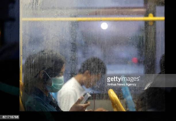YANGON July 24 2017 A girl wearing a mask uses her mobile phone on a bus in Yangon Myanmar July 24 2017 One person out of 13 infected with seasonal...