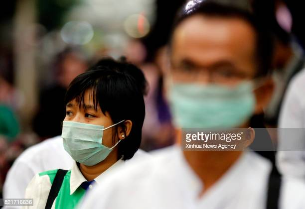 YANGON July 24 2017 People wearing masks wait for buses at a bus stop in Yangon Myanmar July 24 2017 One person out of 13 infected with seasonal...
