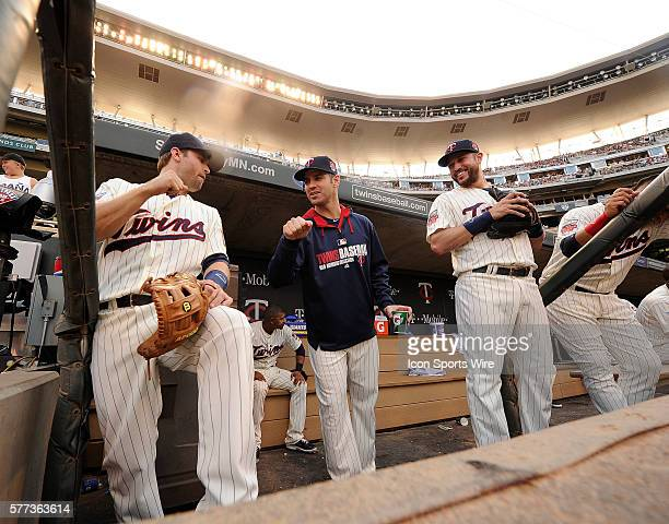 Minnesota Twins injured first baseman Joe Mauer center high fives second baseman Brain Dozier left while third baseman Trevor Plouffe right laughs...