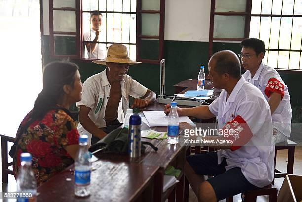 TIANMEN July 27 2016 Residents communicate with medical staff at a middle school which is used as a temporary shelter for people affected by the...