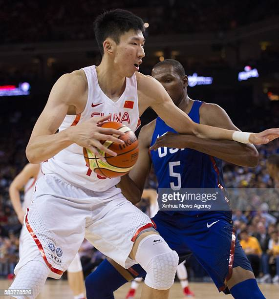 OAKLAND July 27 2016 Zhou Qi left of China controls the ball under pressure by Kevin Durant of the USA during a friendly match at the Oracle Arena in...