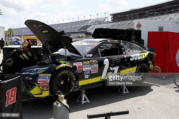 Carl Edwards's crew strips his wrecked race car after being part of multicar wreck during practice for the Sprint Cup Series Coke Zero 400 race at...