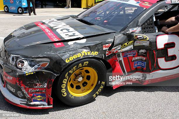 Ryan Newman's crew pushes his wrecked race car after being part of multicar wreck during practice for the Sprint Cup Series Coke Zero 400 race at...