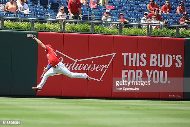 Budweiser billboard as a Phillies outfield leaps to field a fly ball during a Major League Baseball game between the Atlanta Braves and the...