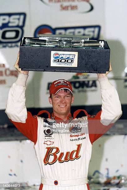 Dale Earnhardt Jr raises the trophy over his head while in victory lane at Daytona International Speedway after winning the Pepsi 400 NASCAR Cup race