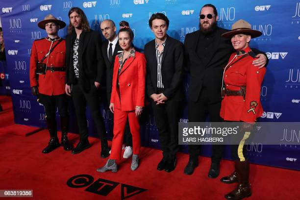 July Talk poses with RCMP as they arrive on the red carpet before the JUNO awards at the Canadian Tire Centre in Ottawa Ontario on April 2 2017 / AFP...