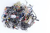 Jumbled pile of old electrical cords and connectors for electronic devices awaiting discard viewed from above on white