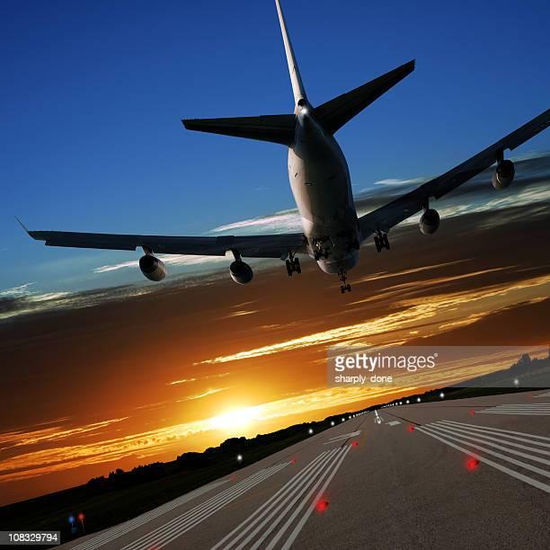 XL jumbo jet airplane landing at sunset