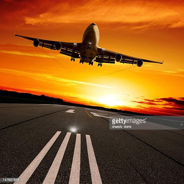 XXL jumbo jet airplane landing at sunset