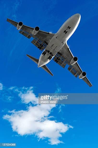XL jumbo jet airplane landing in bright sky
