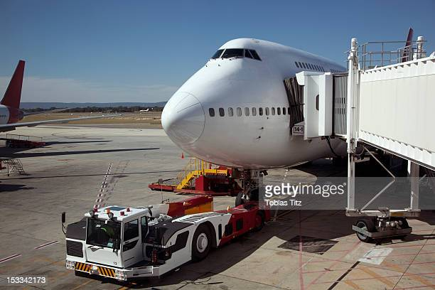 Jumbo jet attached to boarding bridge with tug in front
