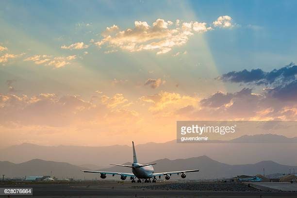 Jumbo Jet on the runway at sunset