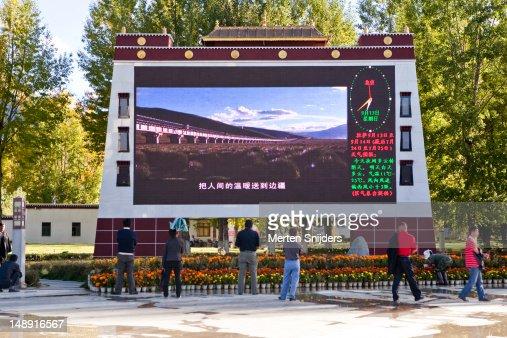 Jumbotron on Potala Square showing trans Tibetan railway construction video clips.