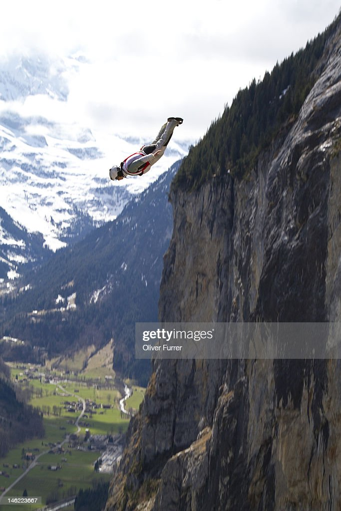 BASE jump girl diving from cliffs : Stock Photo