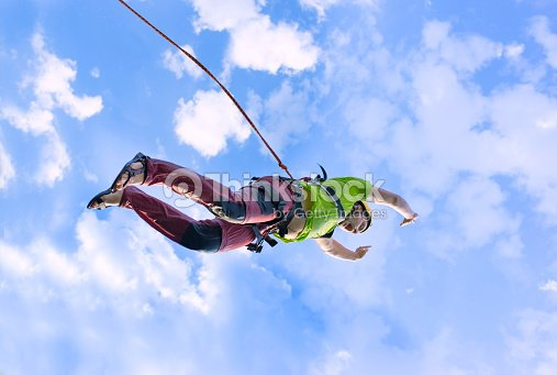 jump rope from a high rock in the mountains ストックフォト thinkstock
