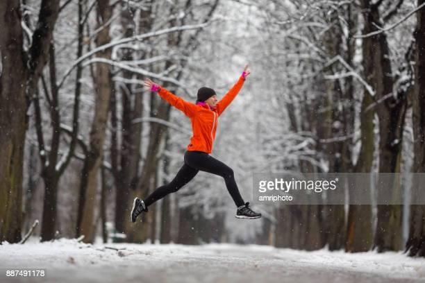Springen! -Seite Ansicht Frau springen in Gasse mit Schnee im Winter