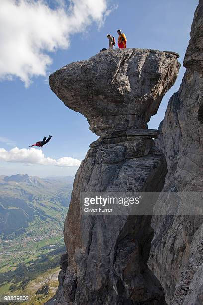 BASE jumper diving down from a distinctive cliff.