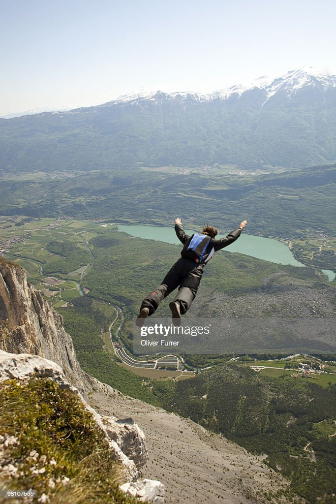 BASE jumper diving down the cliff and flying out.