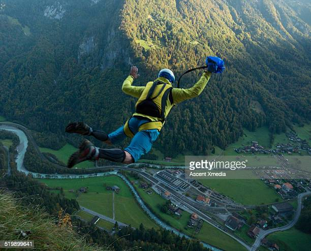 BASE jumper in mid-air flight from cliff, valley