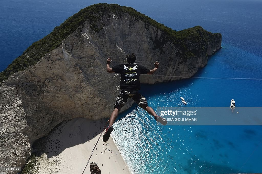 A jumper jumps from a platform atop the rugged rocks overlooking the azure waters of Navagio beach, one of the Greece's most renowned leisure spots on the popular tourist island of Zakynthos on June 23, 2014. This is rope jumping -- part diving, part rock climbing, with a touch of engineering. The aim of the project is to dream jump in 80 places with most ravishing nature and architecture all over the world .They plan to stage their next leaps at a cave complex in Croatia, a French viaduct, skyscrapers in Las Vegas and Johannesburg, and the Grand Canyon.