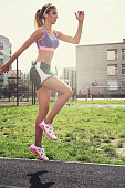 A young beauty athletic woman in sportswear jumping up at outdoor. Warming-up before training
