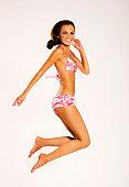 a beautiful brunette girl wearing bikini jumping up on white background