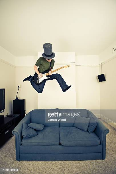 Jumping guitarist in giant top hat, above sofa