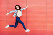 Excited girl is jumping against a red wall