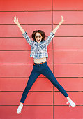 Excited happy woman is jumping against red wall