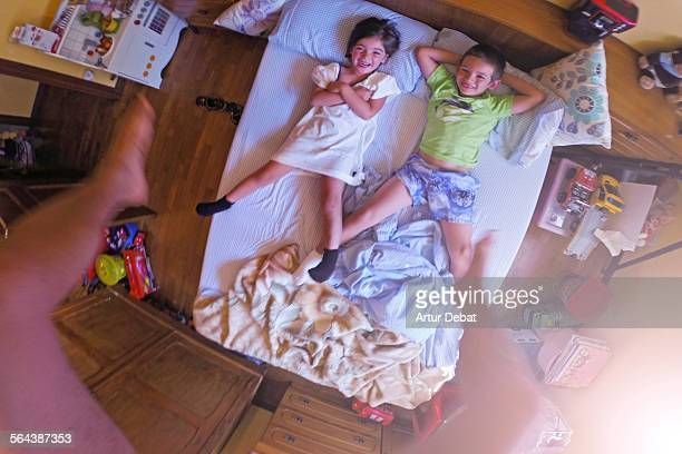 Jumping on the bed with kids from point of view.