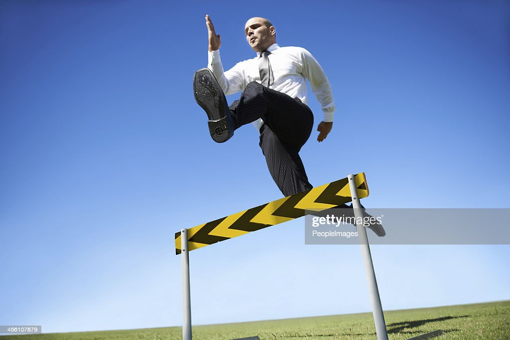 Jumping over business hurdles : Stock Photo