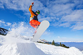 Jumping snowboarder from mountain hill in winter