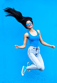Jumping young woman in blue in front of blue wall background