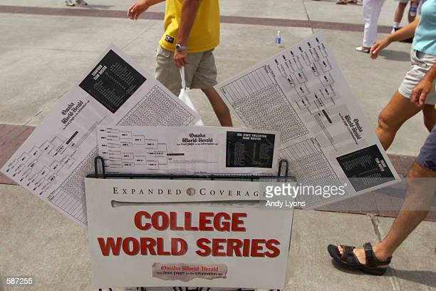 Fans walk behind team fan cards and brackets for the NCAA World Series in front of Rosenblatt Stadium in Omaha Nebraska the site of the NCAA World...