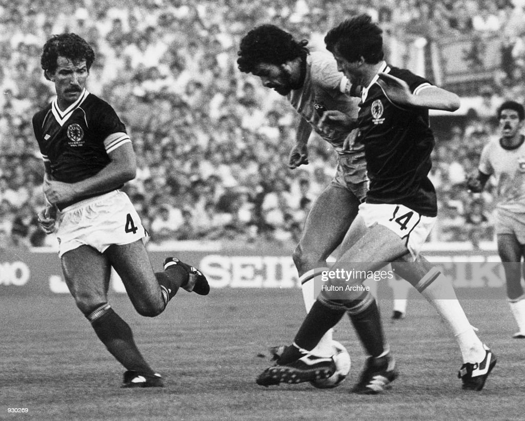 Socrates of Brazil moves in between Graeme Souness and David Narey of Scotland during the FIFA World Cup Finals match played at the Estadio Benito...