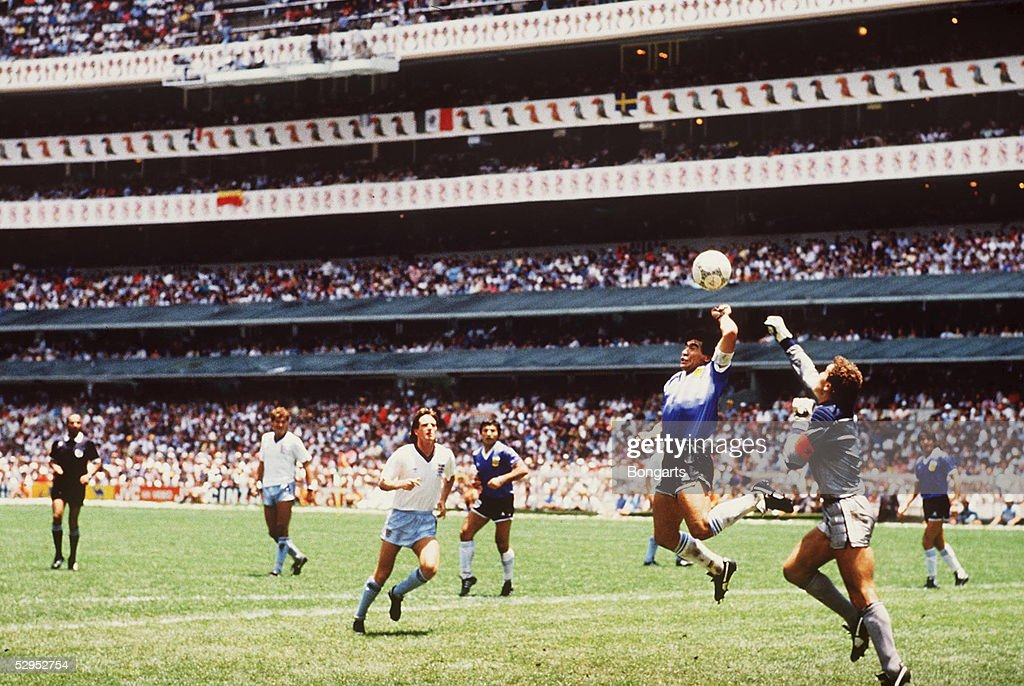 Diego Maradona of Argentina handles the ball past Peter Shilton of England to score the opening goal of the World Cup Quarter Final at the Azteca...