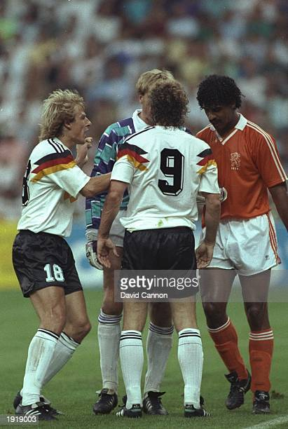 Jurgen Klinsmann and Rudi Voller both of West Germany and Frank Rijkaard of Holland in discussion with the referee during the World Cup match in...