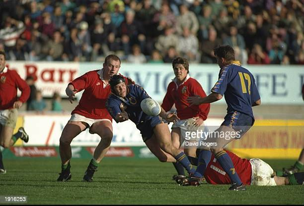 Scott Hastings of the British Lions lies on the ground with a broken jaw as team mate Dean Richards tackles Josh Kronfield of Otago during the Lions...