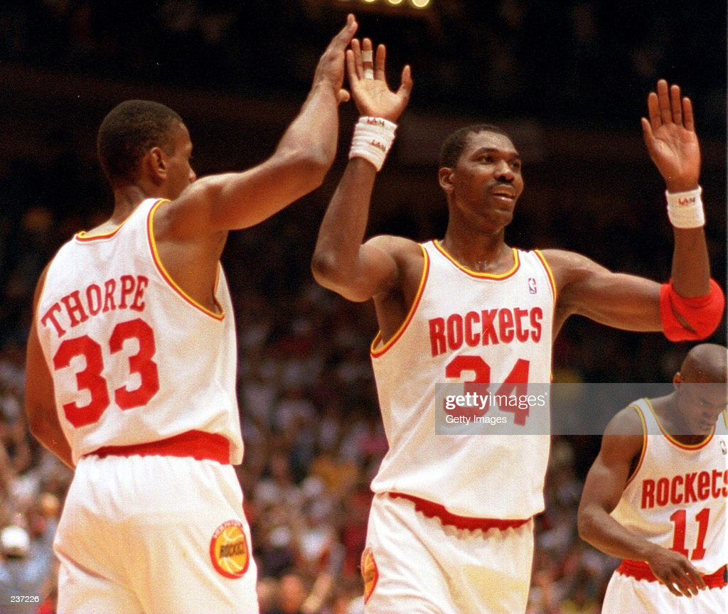 HOUSTON ROCKETS OTIS THORPE AND HAKEEM OLAJUWON EXCHANGE HIGH