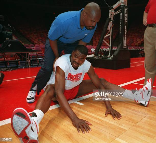 STRENGTH AND CONDITIONING COACH ROBERT BARR HELPS ROCKET CENTER HAKEEM OLAJUWON STREACH FOLLOWING HOUSTON''S