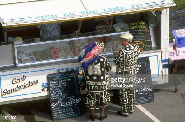 A Pearly King and Queen stand at a sandwich bar during the Derby at Epsom racecourse in Epsom England Mandatory Credit Mike Cooper/Allsport