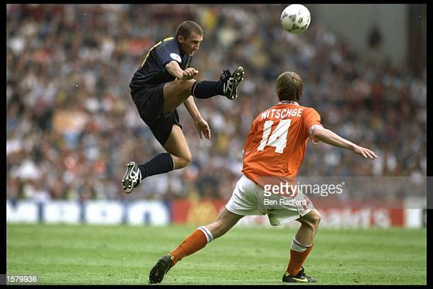Billy McKinlay of Scotland in full flight is shadowed by Richard Witchge of Holland during the European soccer championship game between Holland and...