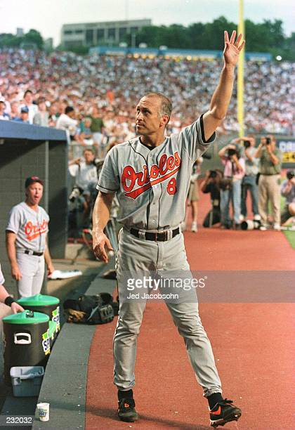 Cal Ripken Jr of the Baltimore Orioles waves to the crowd at the end of the fifth inning after breaking the world record of Sachio Kinugasa of Japan...