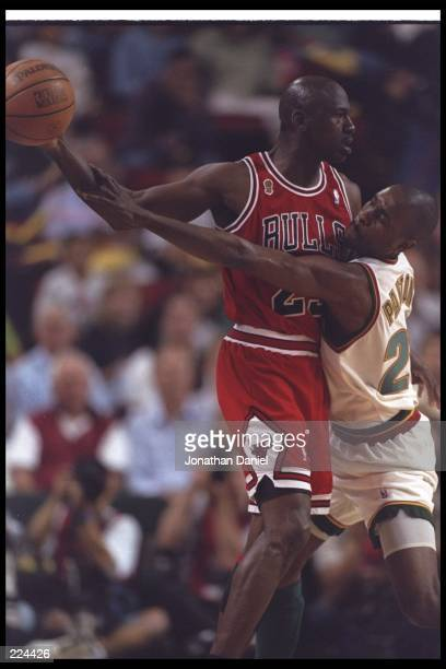 Guard Michael Jordan of the Chicago Bulls and guard Gary Payton of the Seattle SuperSonics tangle up during Game Four of the NBA finals at the Key...