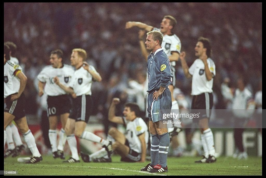 <a gi-track='captionPersonalityLinkClicked' href=/galleries/search?phrase=Paul+Gascoigne&family=editorial&specificpeople=211121 ng-click='$event.stopPropagation()'>Paul Gascoigne</a> of England expression tells the story as the Germans celebrate in the background during the European soccer championships semi final match between England and Germany at Wembley Stadium, London. Germany won the match after extra time in a penalty shoot out by 1(6) 1(5). Mandatory Credit: Stu Forster/Allsport UK