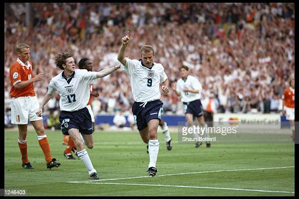 Steve McManaman helps Alan Shearer celebrate his second goal for England against Holland in the Group A match at Wembley during the European Football...