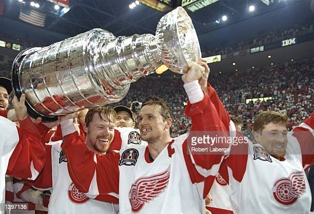 Centers Steve Yzerman and Kris Draper of the Detroit Red Wings celebrate with the Stanley Cup after a playoff game against the Philadelphia Flyers at...