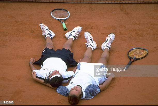 Ruxandra Dragomir of Romania and Iva Majoli of Croatia lie exhausted on the clay after the ladies singles quater final at the Roland Garros French...