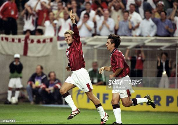David Beckham of England celebrates with team mate Gary Neville after curling in a freekick in the World Cup group G game against Colombia at the...